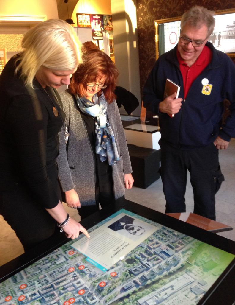 Samtidigt som boken presenterades så visades också det nya innehållet i SVC:s interaktiva skärmar. Tommy Jansson och Svenåke Boström har varit med och skapat nytt innehåll kring gamla brandstationen på Köpmangatan. Cecila Enerud demonstrerar för Maria Åslin och Tommy Jansson.