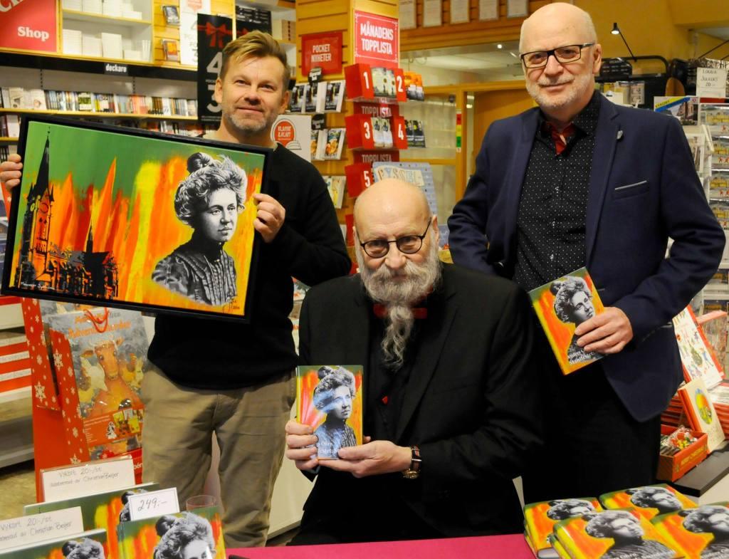 Christian Beijer med omslaget han målat till boken, tillsammans med författaren Anders Öhrn och förläggare Svenåke Boström, vid bokreleasen i bokhandeln vid Vängåvan.